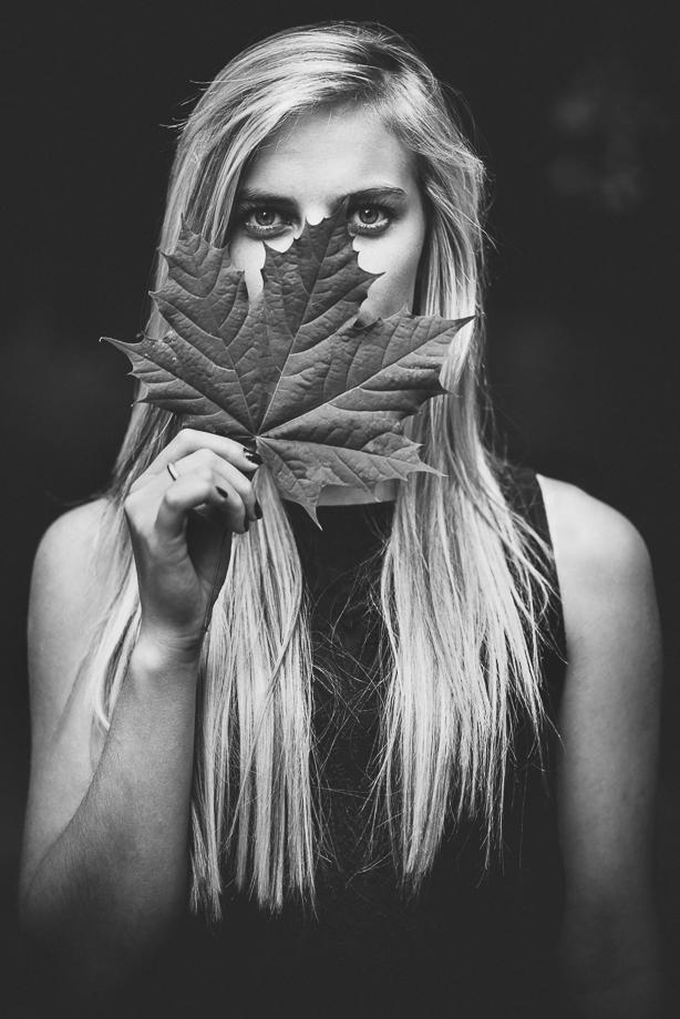 Frau mit Blatt vor Gesicht im Sommer